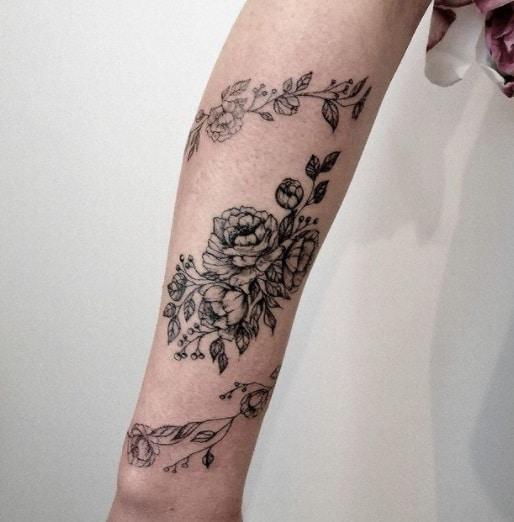 flowers on forearm black ink tattoo