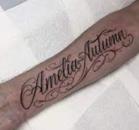 Tattoo with letters on a forearm