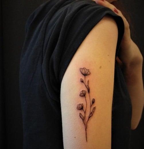 small flower tattoo on arm